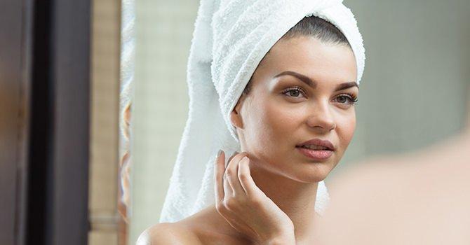 Vrouw met handdoek op hoofd en hand in nek