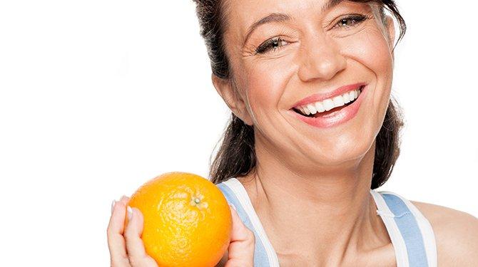 Lachende Vrouw Met Sinaasappel In de Hand