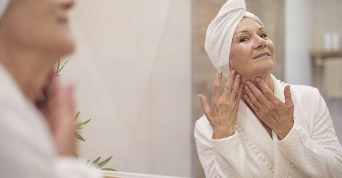 Oudere vrouw bekijkt gezicht